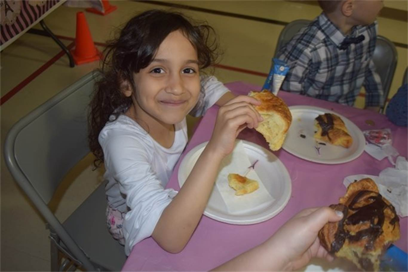 Grade 1 student Millvina Athnel enjoys a chocolate covered croissant during St. Luke Catholic Elementary School's A day in Paris event on May 8. Photo by Laura Lennie, Stoney Creek News