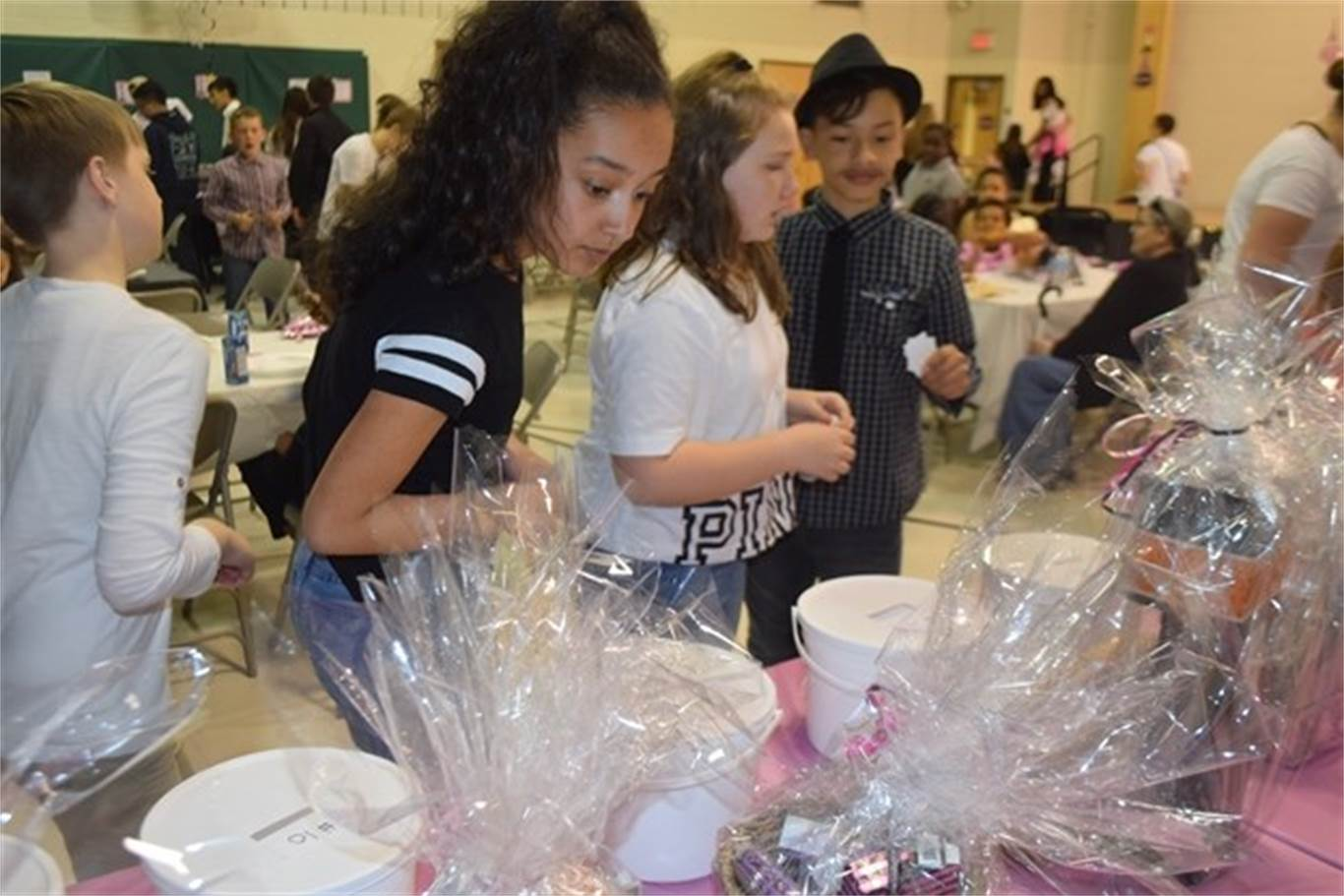 Grade 6 student Lauren Paredes, middle, looks at a few of the many raffle prizes up for grabs at St. Luke Catholic Elementary School's A day in Paris event on May 8. Photo by Laura Lennie, Stoney Creek News